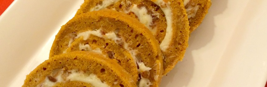 pumpkin roll sliced into pinwheels and arranged in a row in a white platter